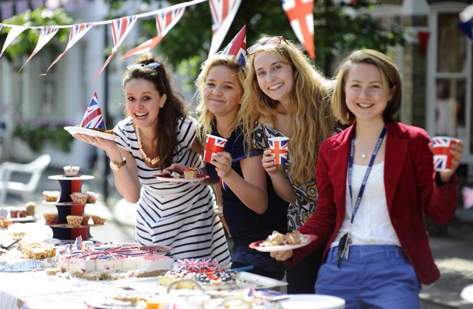 People pose at a street party in Fulham, London. REUTERS/Ki Price