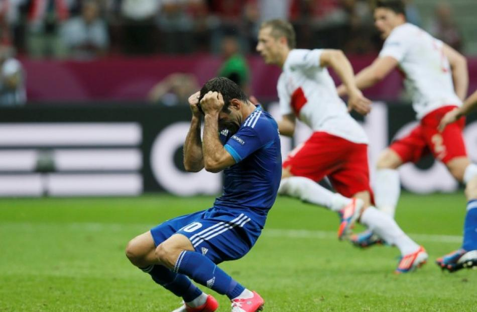 Greece's Giorgos Karagounis reacts after his penalty was saved by Poland's substitute goalkeeper...