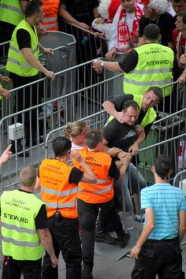 Security personel scuffle with supporters trying to force entry at the match between Poland and...