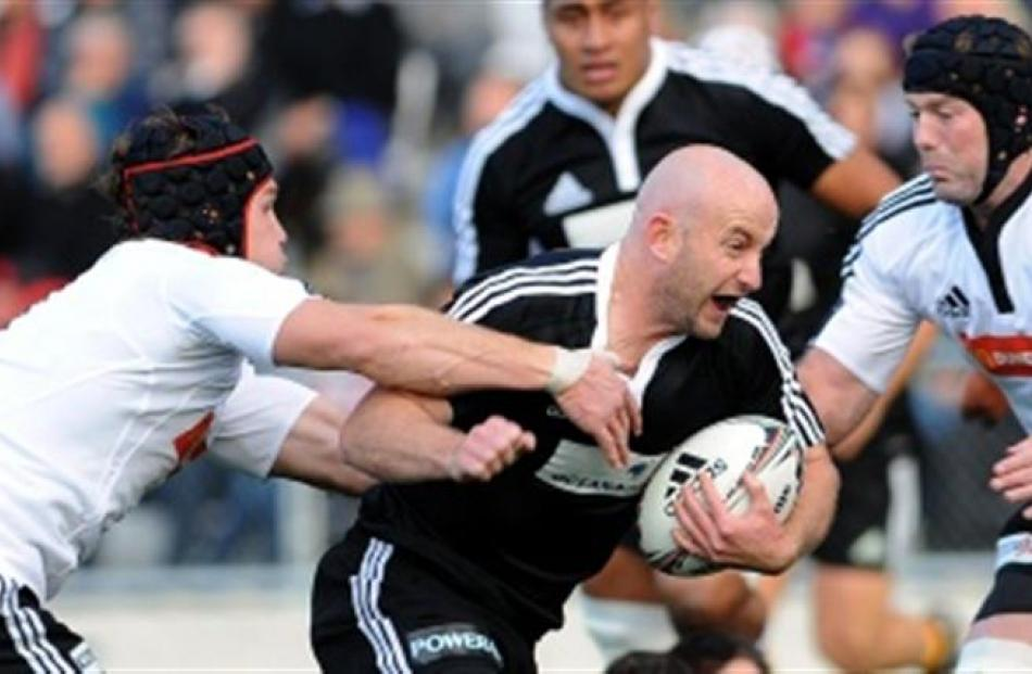 North Island halfback Brendon Leonard tries to barge through the South Island defence of Matt...