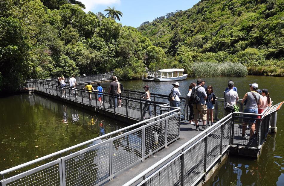 Visitors cross the lower dam on a raised boardwalk.