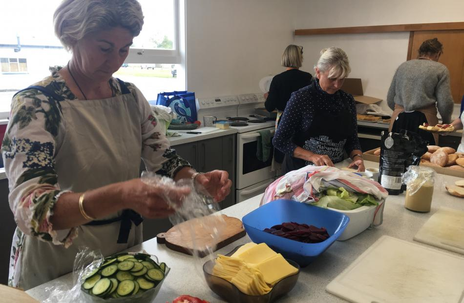 Ainsley Burton (left) and Francie Winter were part of a team of volunteers preparing lunch for...