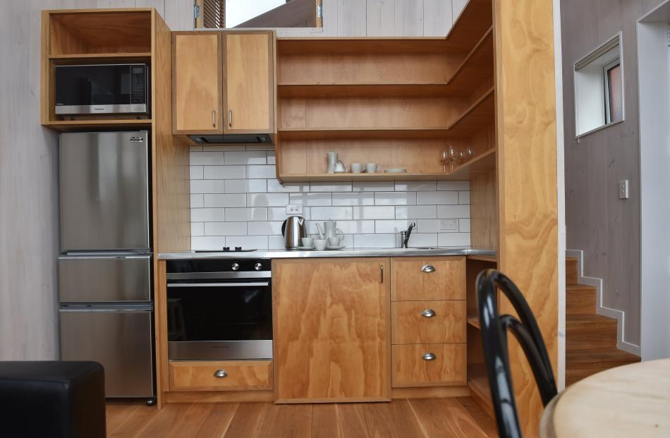 The kitchen in the larger unit, with stairs at right leading up to the bedroom. A combination...