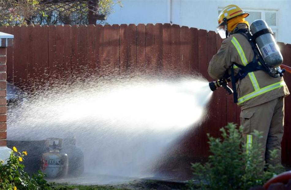 A firefighter hoses down two 9kg gas bottles  at the scene.