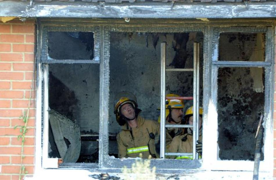 Firefighters inspect the damage inside a Gordon Rd, Mosgiel, house after two gas bottles exploded...