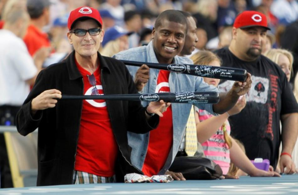 Actor Charlie Sheen (L) and his friend Tony Todd show off bats given to them by players from the...