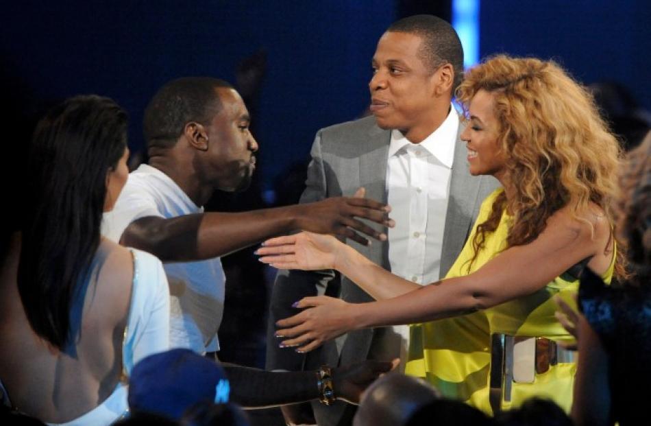 Singer Beyonce (R) congratulates Kanye West as rapper Jay-Z (rear) and actress Kim Kardashian (L)...