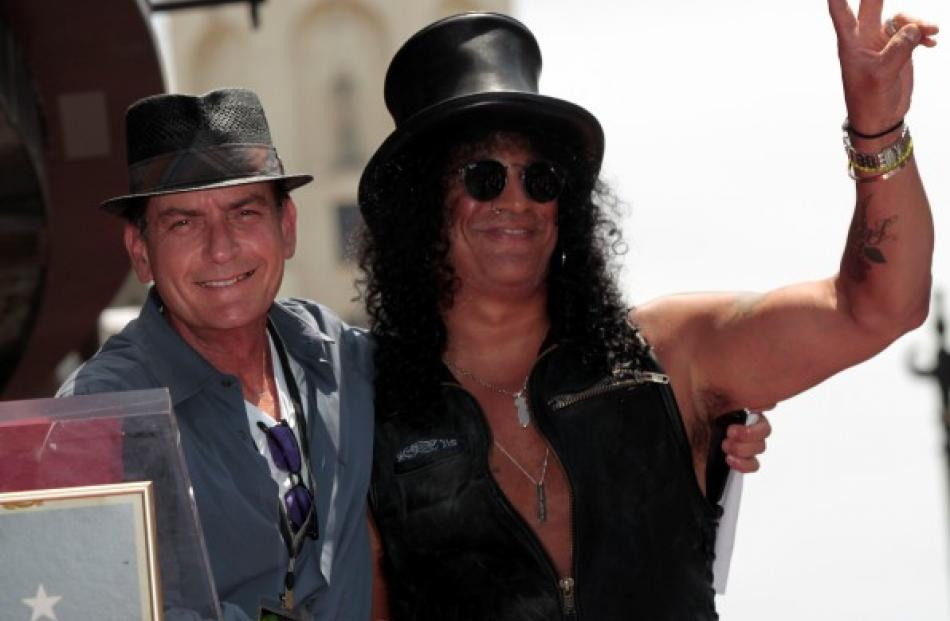 Musician Slash (R) gestures next to actor Charlie Sheen before unveiling his star on the Walk of...