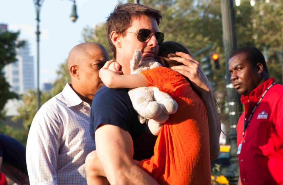 Actor Tom Cruise carries his daughter Suri into the Chelsea Piers sports facility in New York....