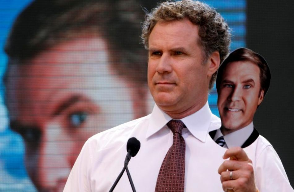 Actor Will Ferrell holds a cutout placard of his face during a mock 'whistle stop tour' press...