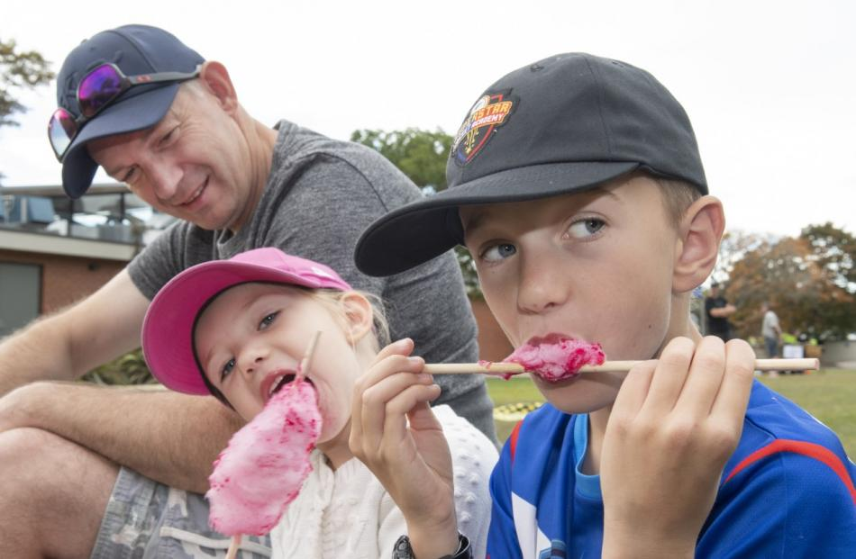 Richard Clark watches his children Isobelle, 4, and Jack, 9, devour candy floss.