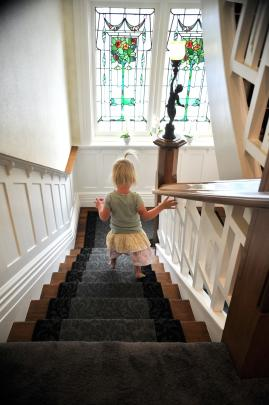 Harper Simms (3) descends the stairs, passing stained glass windows that used to be in an old...