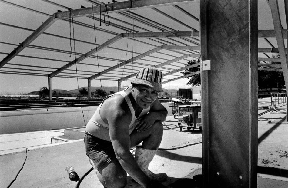 Site foreman Peter Penita puts the finishing touches on the concrete work for the roof at the...
