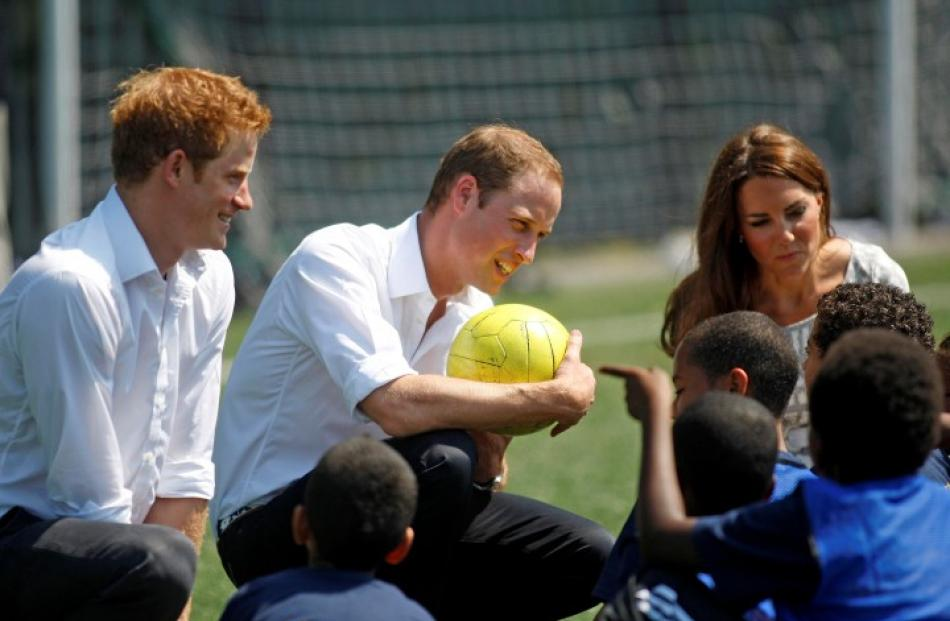 Britain's Catherine (R), Duchess of Cambridge and Prince Harry look on as Prince William (C)...
