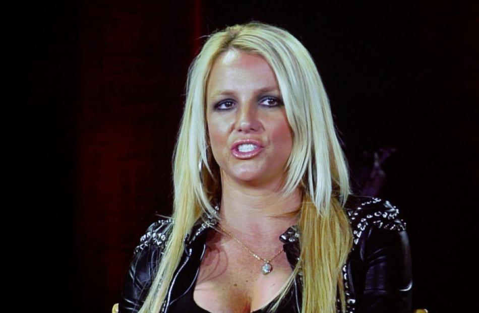 Britney Spears, a judge from 'The X Factor', is pictured on a video screen via satellite from...
