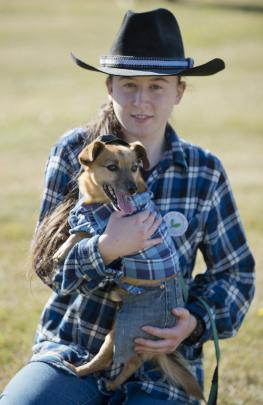 Keziah O'Neill (15), of Waitati, holds her dog Oink (7) after winning best dressed in the owner...
