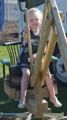 Having a go on a digger made by Ashford Landscaping staff from recycled materials is Annabelle...