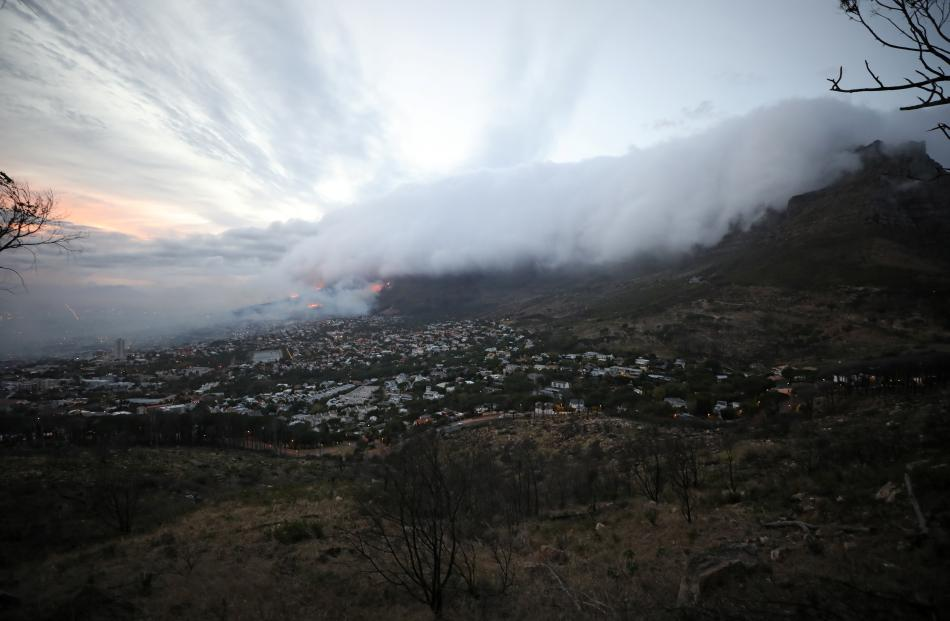 Smoke and clouds cover the city as fires fanned by strong winds continue to spread on the slopes of Table Mountain in Cape Town. Photo: Reuters