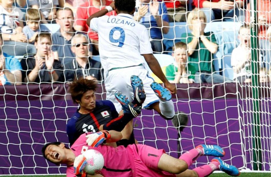 Japan's Daisuke Suzuki (13) falls on his goalkeeper Shuichi Gonda near Honduras' Antony Lozano in...