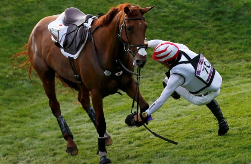 Japan's Yoshiaki Oiwa falls from his horse Noonday de Conde while competing in the cross country...