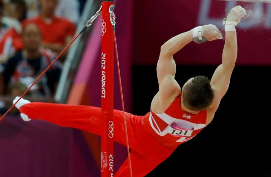 Sam Oldham of Britain falls from the horizontal bar during the men's gymnastics team final.