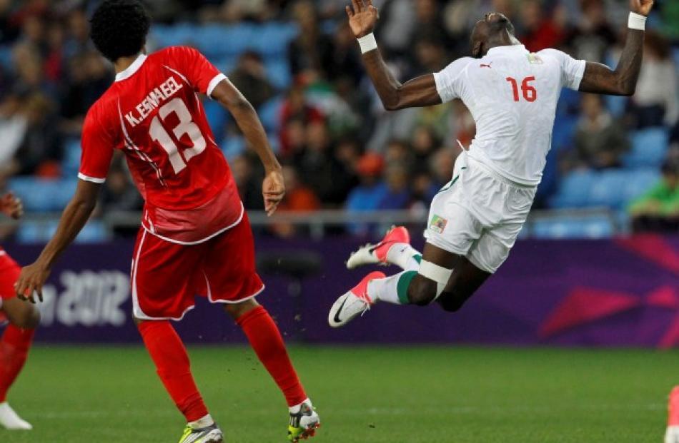 Senegal's Pape Souare (R) falls next to UAE's Khamis Esmaeel during their men's Group A football...