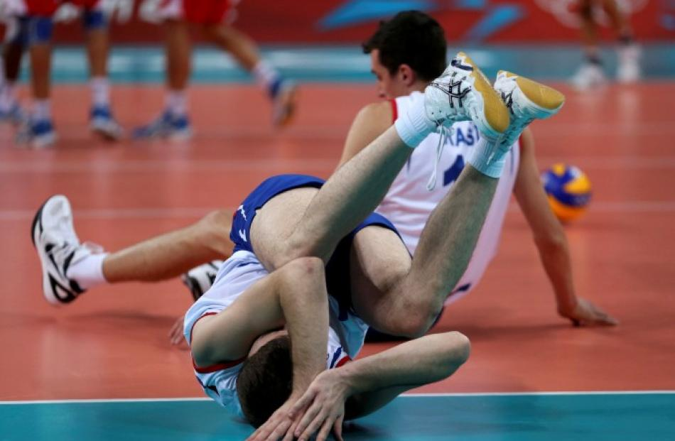 Serbia's Uros Kovacevic (L) and Milan Rasic fall during their men's Group B volleyball match...