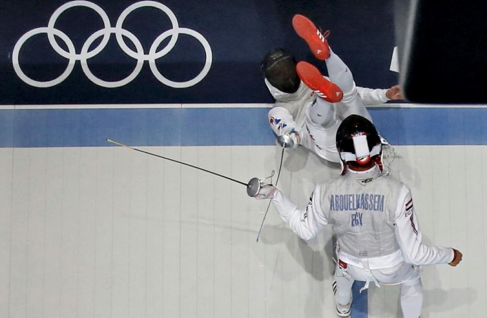 South Korea's Choi Byungchul (top) falls down as he competes against Egypt's Alaaeldin...