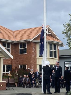 Members of the HMNZS Toroa flag party lower the New Zealand flag in preparation for raising the...