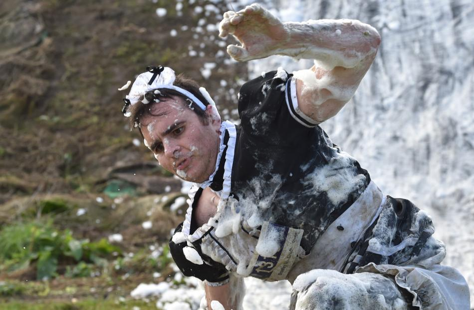 Bradley Croft, dressed in a maid's outfit, emerges from a soapy slide.