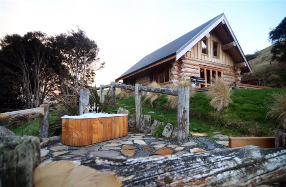 The log cabin, complete with outdoor bath, built by Dave and Janene Divers on their property near...