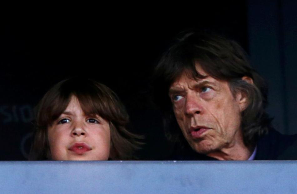 Mick Jagger sits with his son Lucas as they watch athletics events during the London 2012 Olympic...