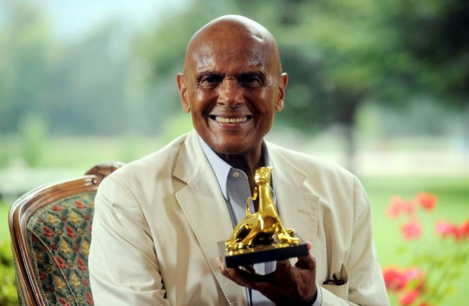 US singer and actor Harry Belafonte poses with his 'Pardo alla Carriera' award during a photocall...