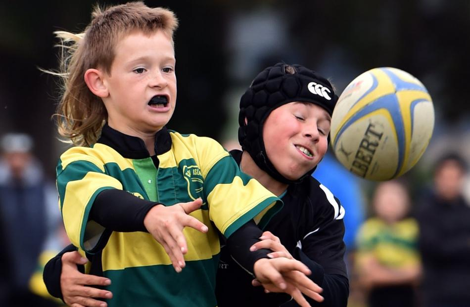 Lachie Shaw (10), of Green Island, is tackled by Pirates defender Archie Rhodes (10).