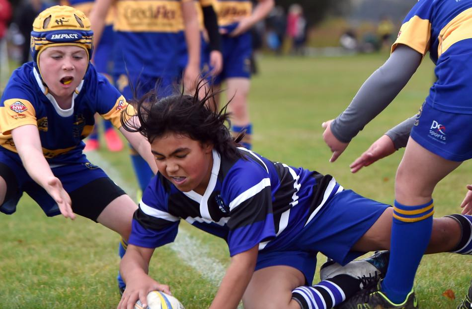Kaikorai year 6 pupil Stacey Karawana (9) scores a try watched by Angus Shaw (10), of Taieri.