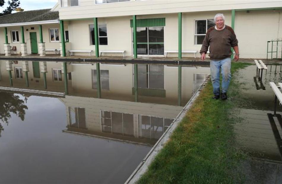 Green supervisor Tim Nichols contemplates the flooded grounds of the Maheno Bowling Club...