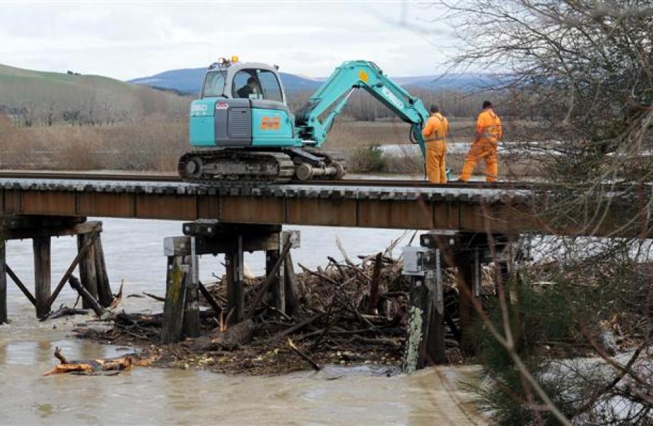 KiwiRail staff clear trees from beneath the Shag River rail bridge, near Palmerston, yesterday....