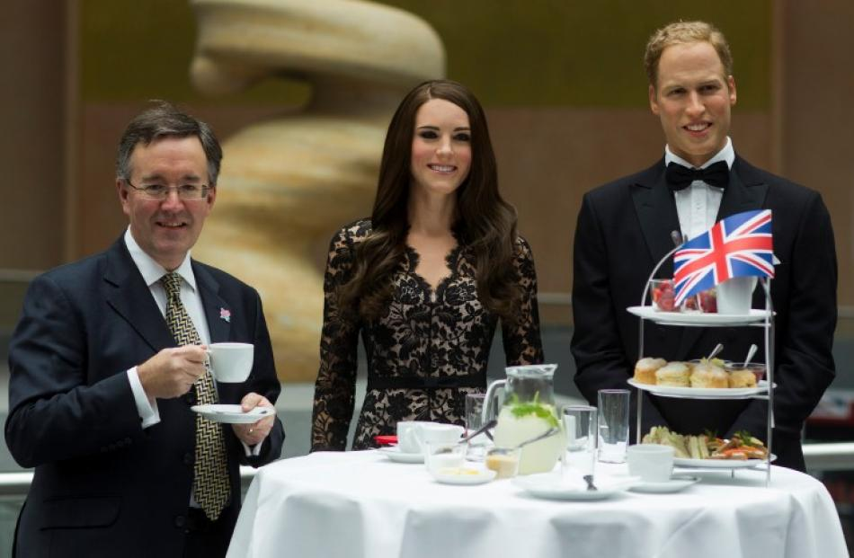 British Vice Ambassador Andrew Noble (L) poses with wax figures of Catherine, Duchess of...