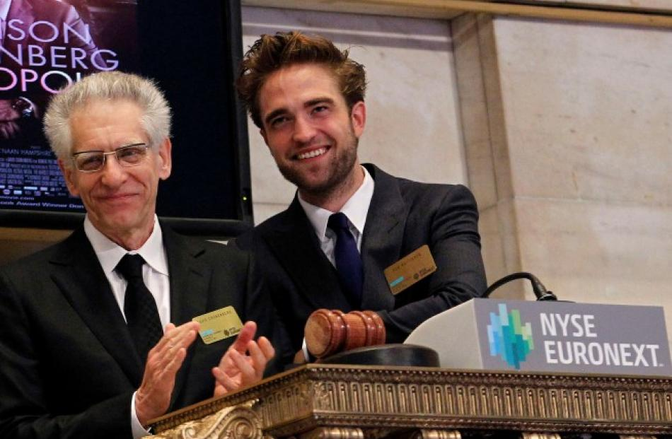 Filmmaker David Cronenberg (L) and actor Robert Pattinson ring the opening bell at the New York...