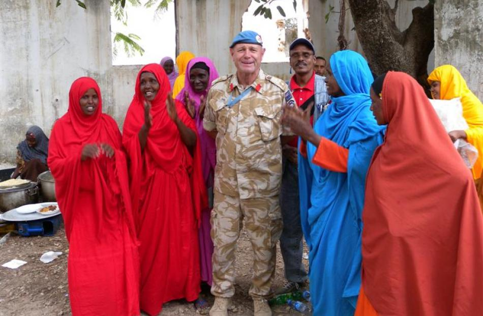 Col Howie with a group of Somali women in bright traditional robes.