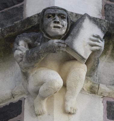 A grotesque depicts a hooded academic holding up a book.