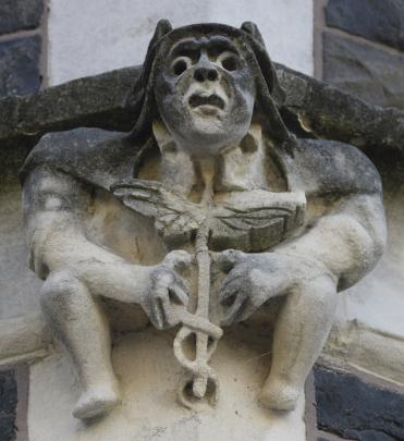 A figure holds medical symbol the caduceus of Mercury with its two wings and snakes. The rod of Asclepius, with one snake and no wings, is also used as a symbol of healing.