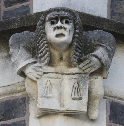 A figure wearing a judicial wig holds the scales of justice.