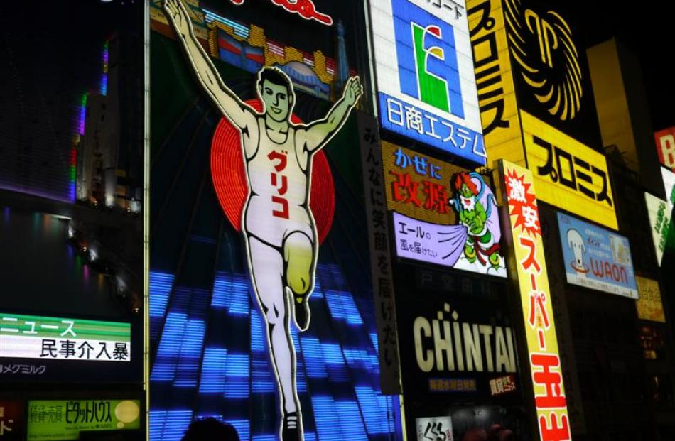 "Dizzyingly bright neon signs and lanterns scream ""okonomiyaki"", the region's specialty dish - a..."