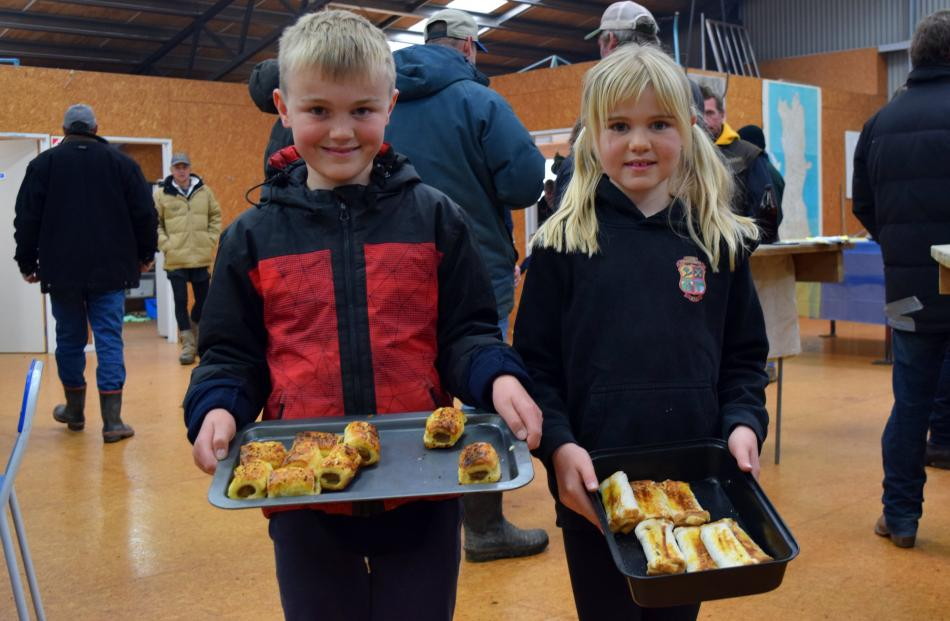 Siblings Blake (9) and Holly (8) Campbell serve snacks to people as the auction runs in the...