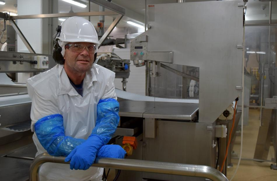 Alliance Group sawman Andrew McLaren relaxes by a BladeStop bandsaw in the Pukeuri plant last week.