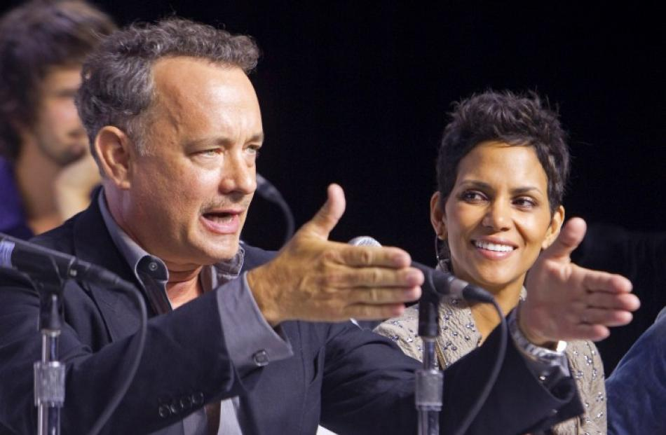 Actor Tom Hanks speaks as actress Halle Berry watches, during a news conference to promote the...