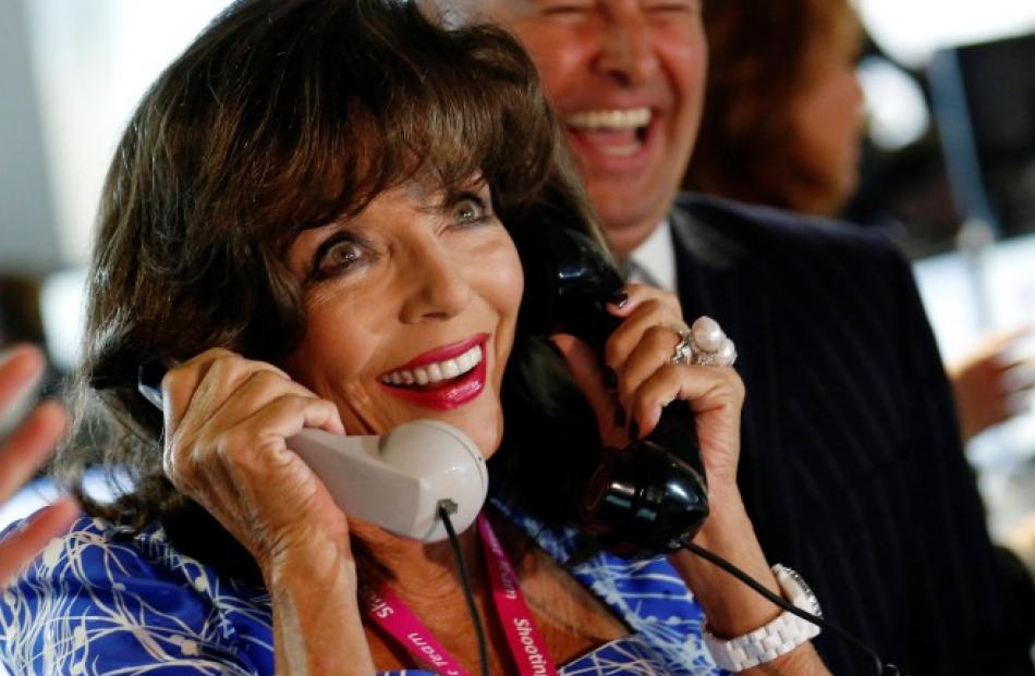 Actress Joan Collins speaks on a telephone as she takes part in a charity event on the trading...