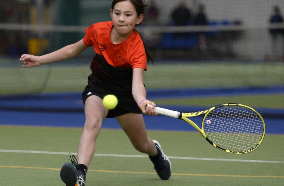 Aliyah Daly (10), of Christchurch, races forward to power a shot down the line.