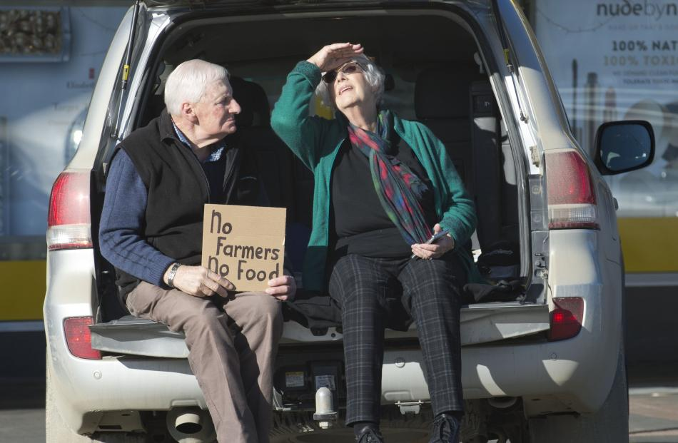 """Sheep and beef farmers Trevor and Ruth Stewart, of Mokoreta, hold a """"no farmers , no food"""" sign..."""